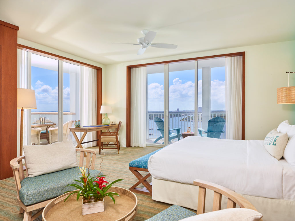 Room contemporary furnishings with a sea and sky color palette, one king bed, two armchairs, table and two large windows and balcony
