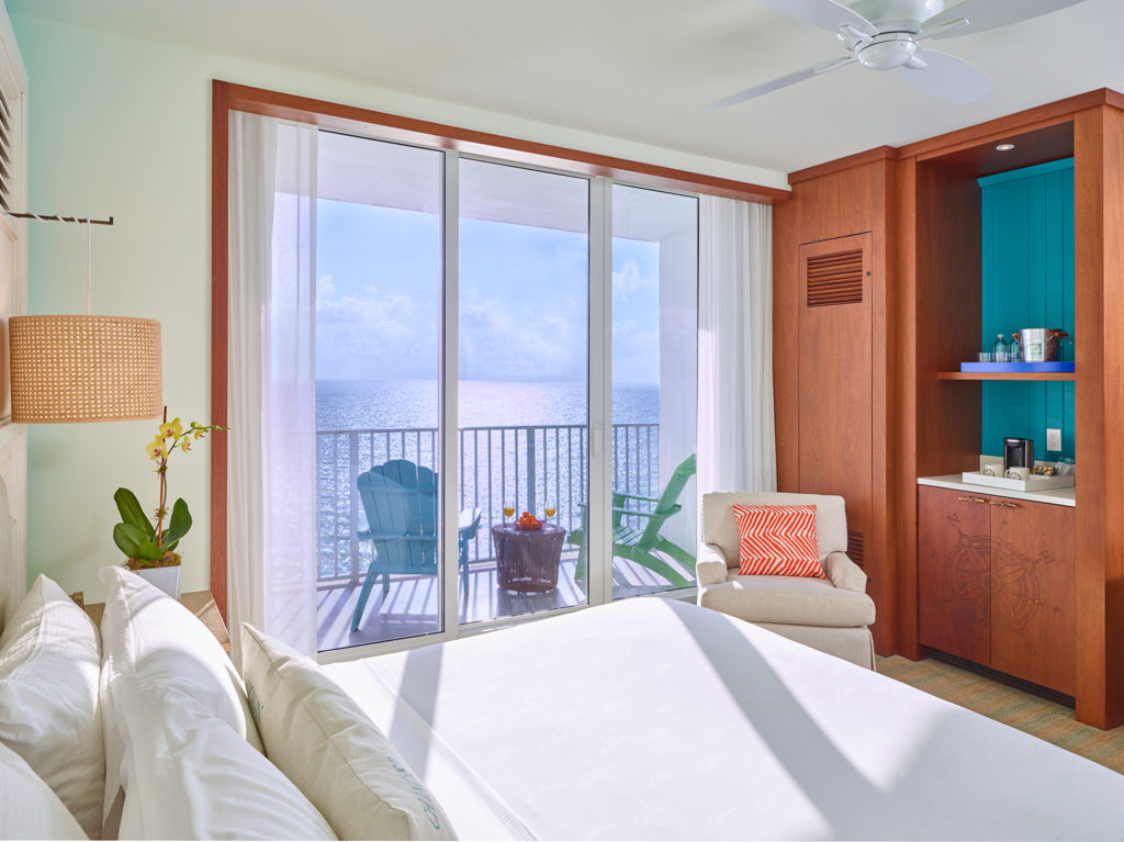 Room with queen bed, armchair, large window and balcony with partial views