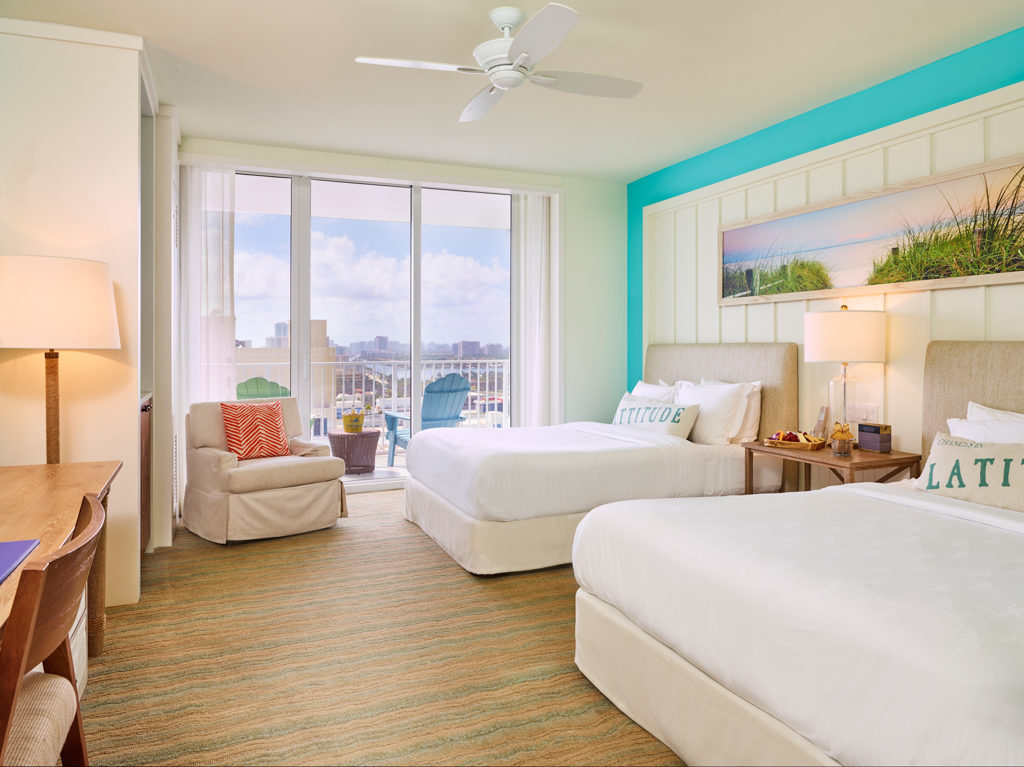 Room contemporary furnishings with a sea and sky color palette and two queen beds, armchair, table, large window and balcony with partial views
