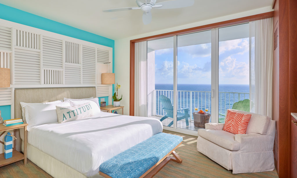Room contemporary furnishings with a sea and sky color palette, queen bed, armchair, large window and balcony