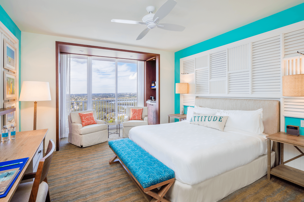 Room contemporary furnishings with a sea and sky color palette and king bed, two armchairs, table and large window