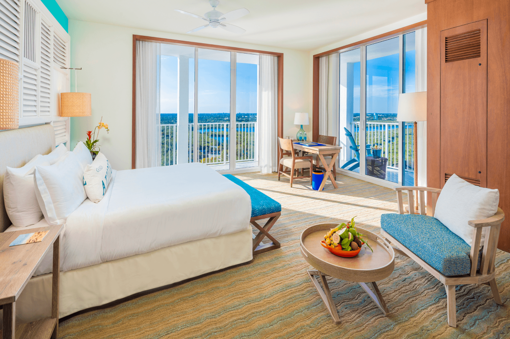 Room contemporary furnishings with a sea and sky color palette, one king bed, armchair, table and two large windows and balcony