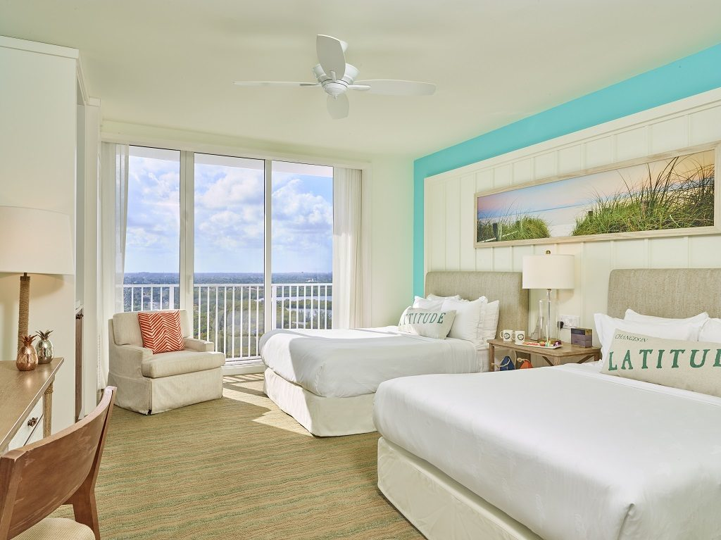 Room contemporary furnishings with a sea and sky color palette and two queen beds, armchair and large window
