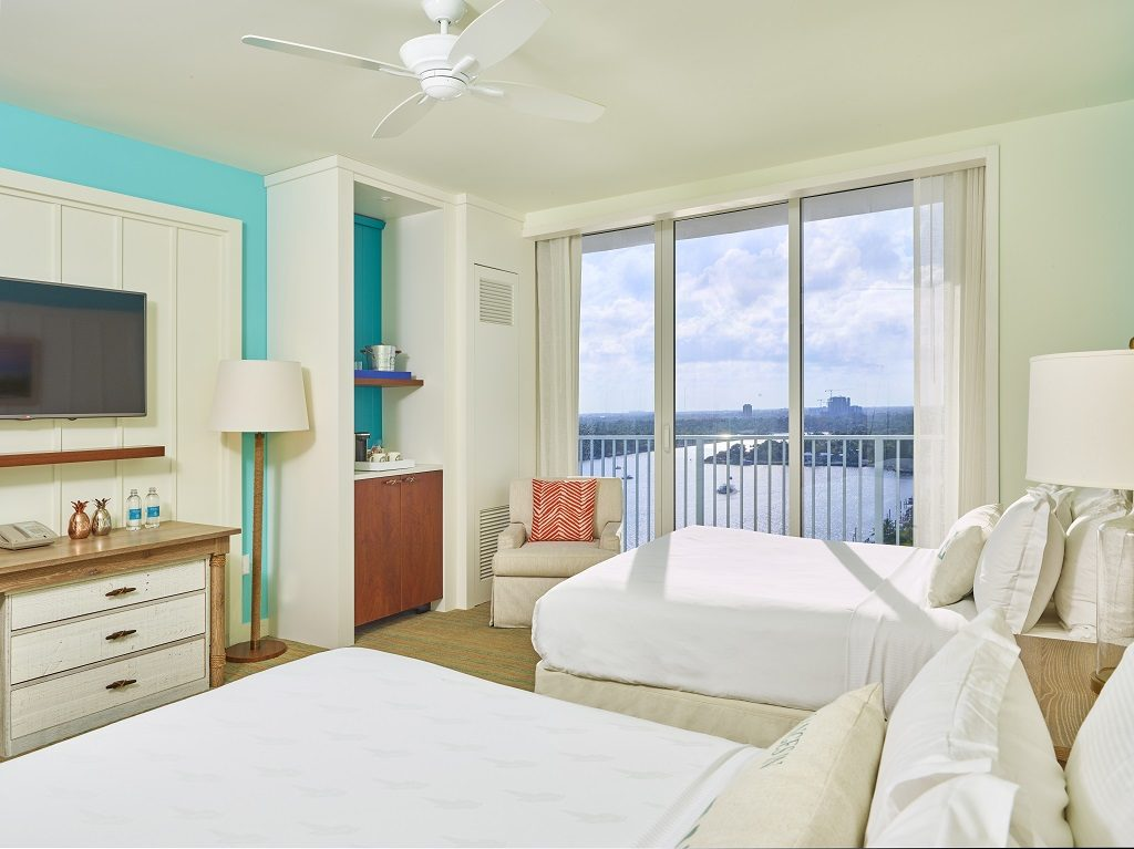 Room contemporary furnishings with a sea and sky color palette and two queen beds, armchair, tv, and large window
