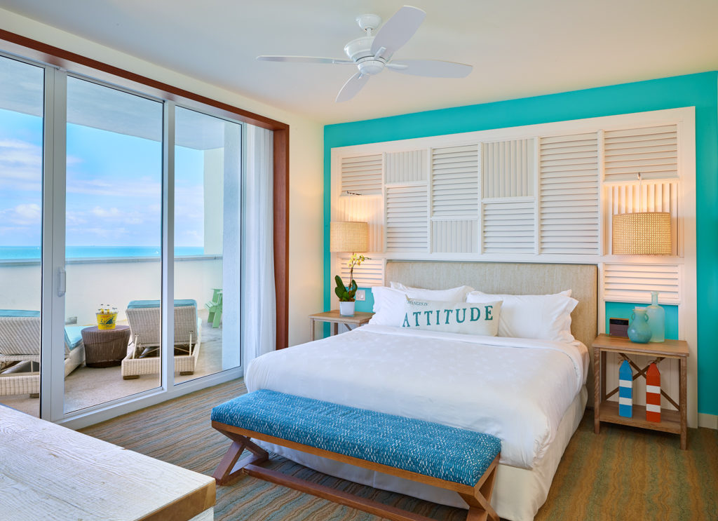 Room contemporary furnishings with a sea and sky color palette, one king bed, large window and veranda