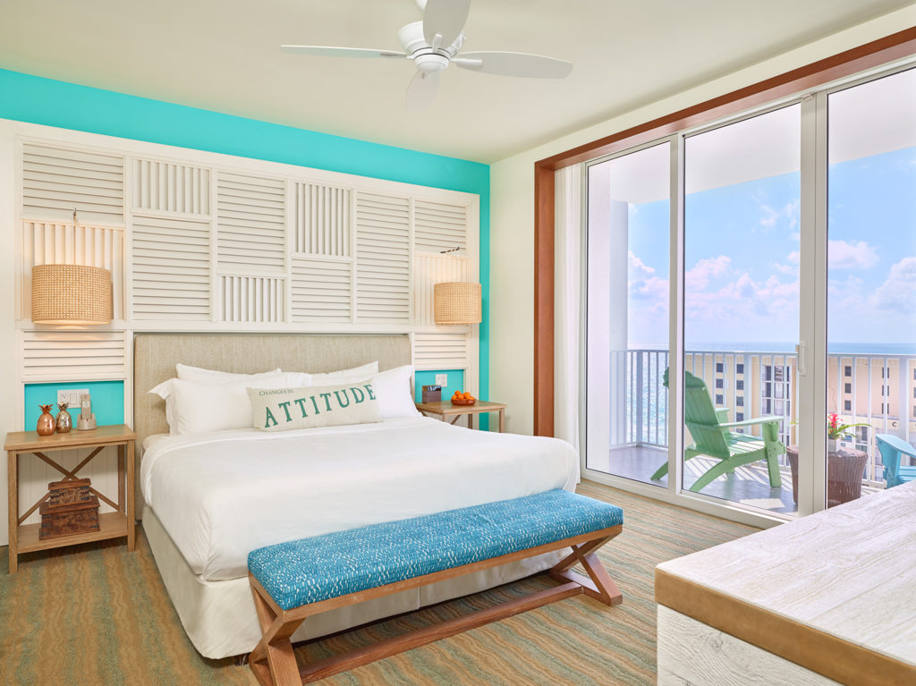 Room contemporary furnishings with a sea and sky color palette, one king bed, large window and balcony