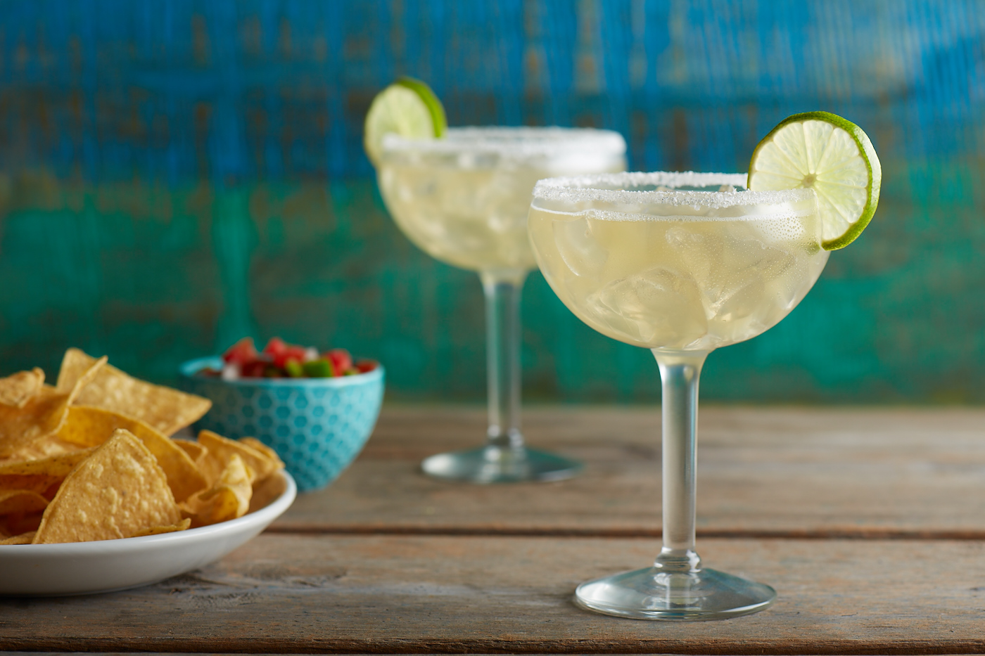 margaritas and chips on a wooden table
