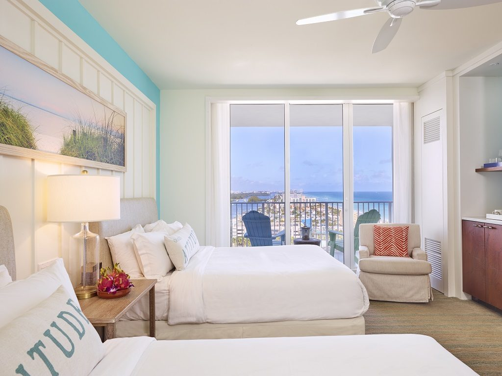 Room contemporary furnishings with a sea and sky color palette and two queen beds, armchair, large window and balcony