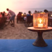 People are sitting at the tables in the evening on the beach