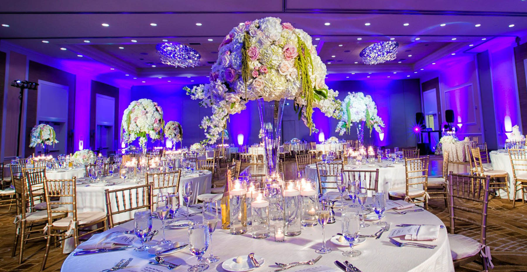 wedding reception table in reception ballroom with blue lights