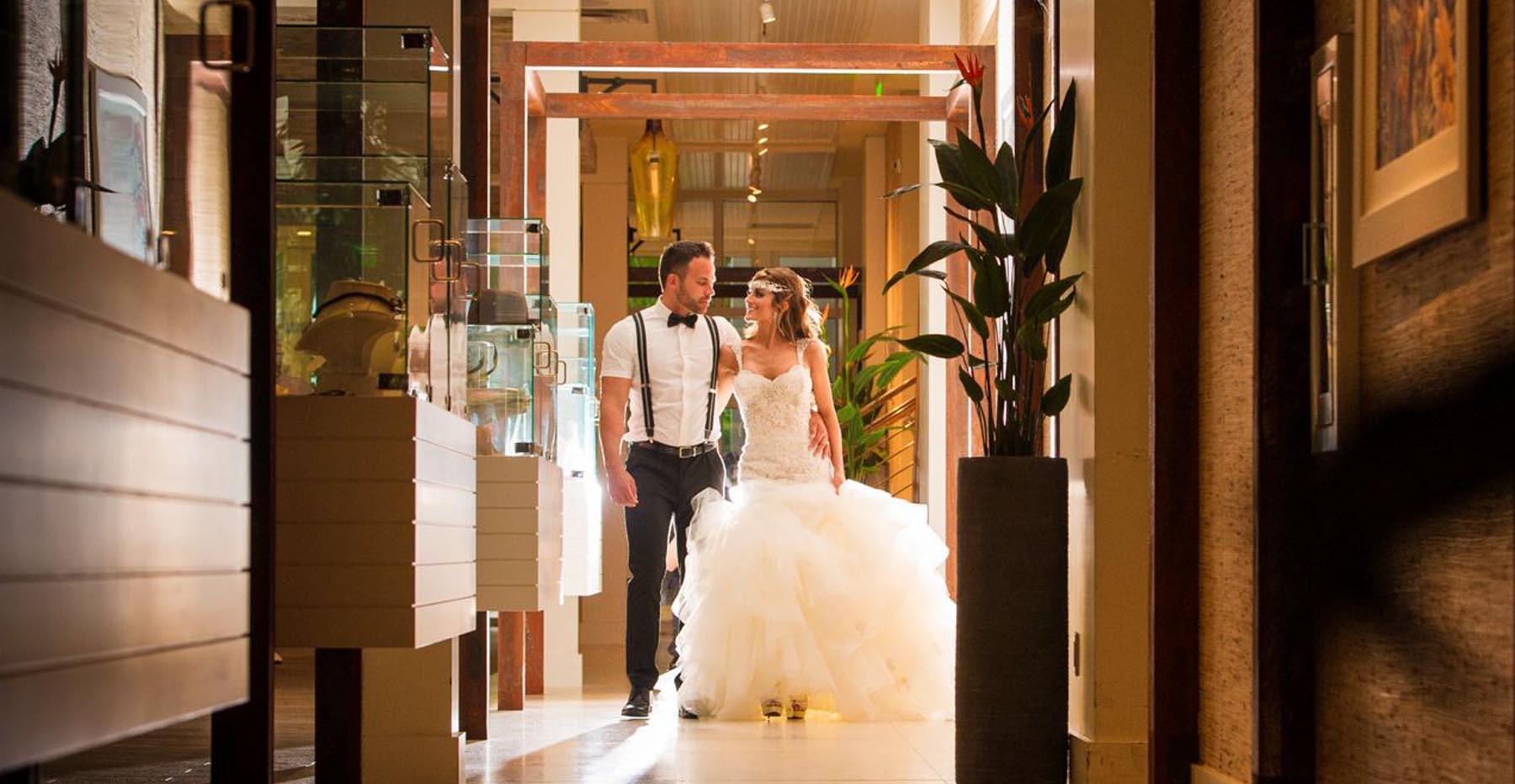 Wedding couple photographed inside down a hallway